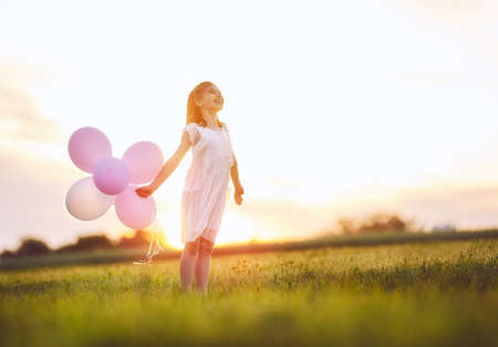 Child is laughing and playing on a meadow at sunset background. Girl with air balloons.