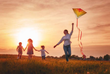 Happy family playing outdoor. Mother and children running on meadow with a kite in the summer on the nature. Stockfoto - 105503934