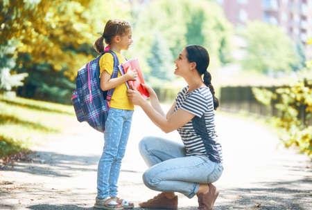 Parent et élève du primaire vont de pair. Femme et fille avec sac à dos derrière le dos. Début des cours. Premier jour d'automne. Banque d'images