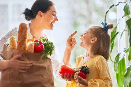 Familieneinkauf. Mutter und ihre Tochter halten eine Einkaufstüte mit Gemüse in der Hand. Standard-Bild - 106032815