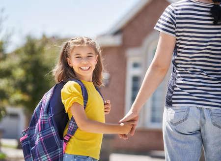 Ouder en leerling van de basisschool gaan hand in hand. Vrouw en meisje met rugzak achter de rug. Begin van lessen. Eerste dag van de herfst.