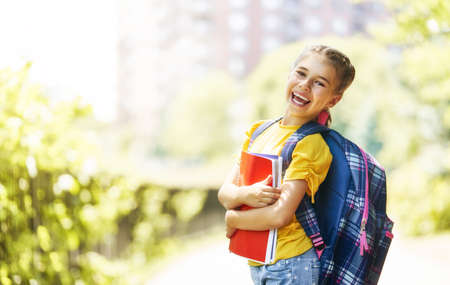 Pupil of primary school with book in hand. Girl with backpack near building outdoors. Beginning of lessons. First day of fall. Zdjęcie Seryjne