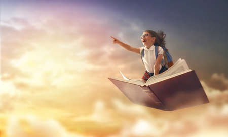 Back to school! Happy cute industrious child flying on the book on background of sunset sky. Concept of education and reading. The development of the imagination. Фото со стока