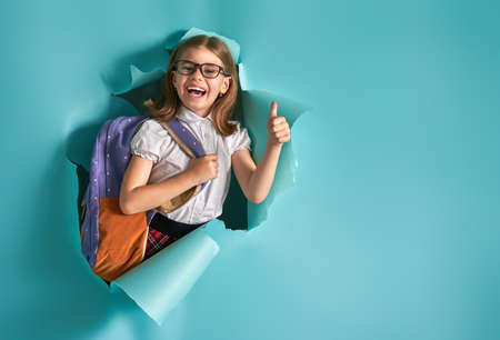 Back to school and happy time! Cute industrious child is breaking through color paper wall. Kid with backpack. Girl ready to study. Stockfoto
