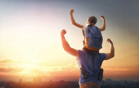 Parent and pupil of primary school on sunset background. Man and girl with backpack behind the back. Beginning of lessons. First day of fall. Standard-Bild