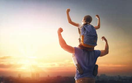 Ouder en leerling van basisschool op zonsondergangachtergrond. Man en meisje met rugzak achter de rug. Begin van lessen. Eerste dag van de herfst.
