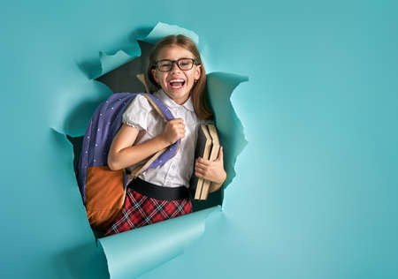 Back to school and happy time! Cute industrious child is breaking through color paper wall. Kid with backpack. Girl ready to study. Stock Photo