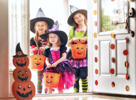 Happy Halloween! Three cute little laughing girls in witches costumes are coming to the house for sweets.