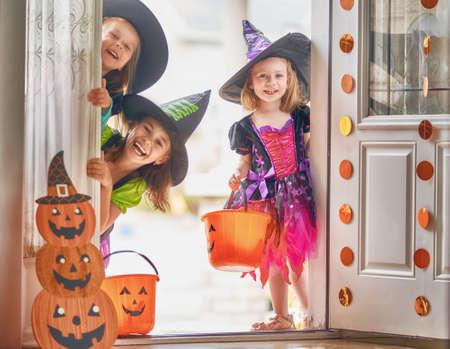 ¡Feliz Halloween! Tres lindas niñas riendo con disfraces de brujas vienen a la casa por dulces.