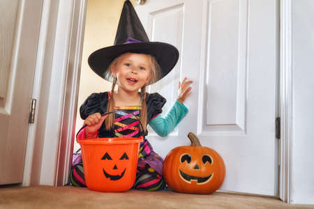 Happy Halloween! Cute little laughing girl in witch costume with a pumpkin. Banco de Imagens