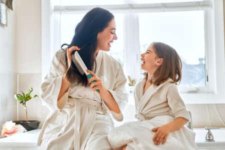 Famille heureuse! Mère et fille enfant fille se peignent les cheveux dans la salle de bain.