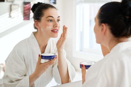 Mooie jonge vrouw die met room voor haar gezicht in de spiegel in badkamers thuis kijkt. Gezichtsbehandeling. Cosmetologie, schoonheid en spa.