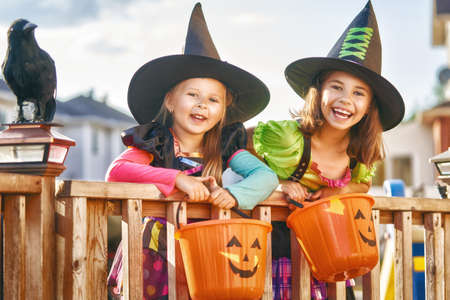 Happy Halloween! Two cute little laughing girls in witches costumes are coming to the house for sweets.