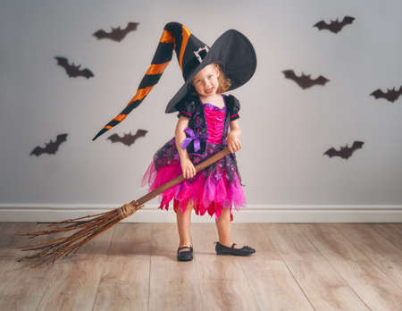 Happy Halloween! Cute little laughing girl in witch costume with a broomstick.