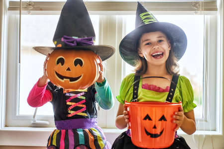 Happy Halloween! Two cute little laughing girls in witches costumes.