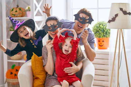 Mother, father and their kids having fun at home. Happy family celebrating Halloween. Children wearing carnival costumes.