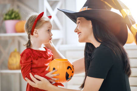 Happy family preparing for Halloween! Young mom and her kid in carnival costumes celebrate the holidays.