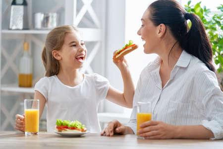 Gesundes Essen zu Hause. Glückliche Familie in der Küche. Mutter und Kind frühstücken.