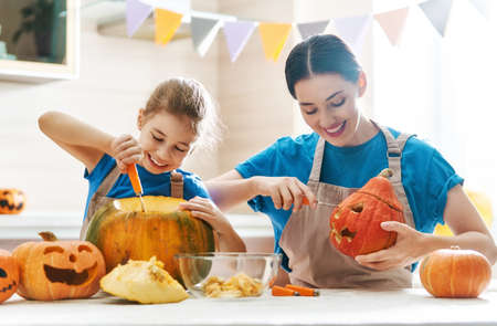 Happy Halloween! Mother and her daughter carving pumpkin. Family preparing for holiday. Banco de Imagens