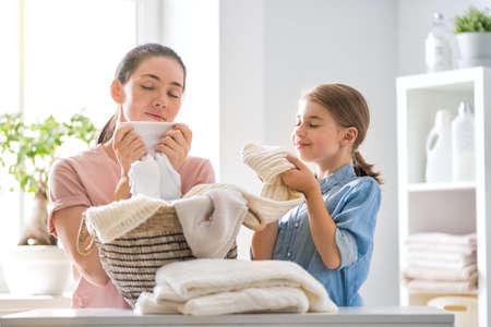 Die kleine Helferin der schönen jungen Frau und des Kindermädchens haben Spaß und lächeln, während sie Wäsche zu Hause machen.