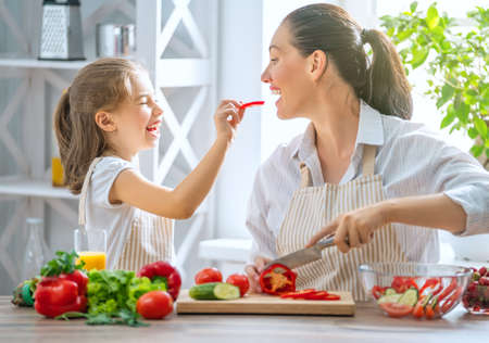 Healthy food at home. Happy family in the kitchen. Mother and child daughter are preparing the vegetables.