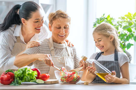 Healthy food at home. Happy family in the kitchen. Grandma, mother and child daughter are preparing the vegetables and fruit. Stockfoto