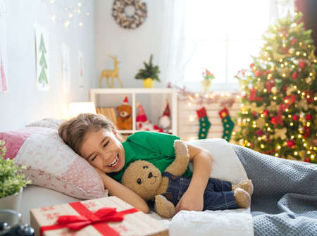 Merry Christmas and Happy Holiday! Cute little child girl sleeping in the bed near tree at home. Stok Fotoğraf