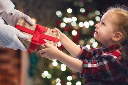 Merry Christmas and Happy Holidays! Hands of Santa Claus giving a x-mas gift to child. Stock Photo