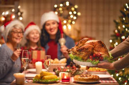 ¡Feliz Navidad! La familia feliz está cenando en casa. Fiesta de celebración y unión cerca del árbol. Foto de archivo