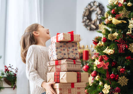 Merry Christmas and Happy Holiday! Cute little child girl with present gift boxes near tree at home.