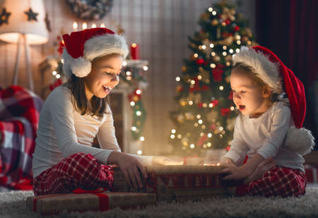Merry Christmas and Happy Holiday! Cute little children girls with present gift box near tree at home. Stockfoto