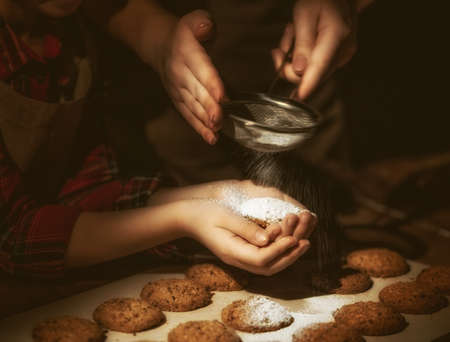 Close up view of bakers are working. Homemade family cookies. Hands of mother and daughter preparing biscuits on wooden table.