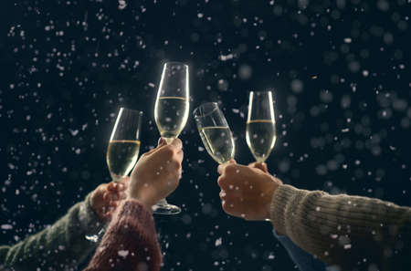Merry Christmas and Happy New Year! Hands of people with wine glasses clinking in snowy winter night. Imagens