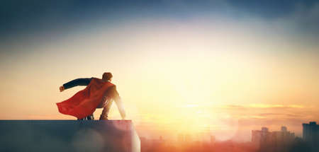 superhero businessman looking at city skyline at sunset. the concept of success, leadership and victory in business. Stock Photo