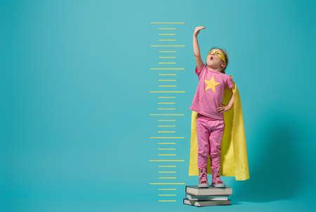 Piccolo bambino che gioca al supereroe. Kid misura la crescita sullo sfondo della parete blu brillante. Concetto di potere della ragazza. Colori giallo, rosa e turchese.