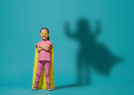 Little child playing superhero. Kid on the background of bright blue wall. Girl power concept. Yellow, pink and  turquoise colors. 版權商用圖片