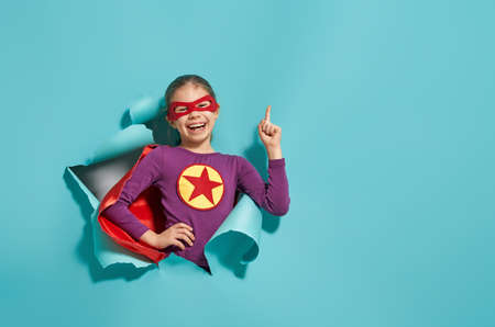Little child is playing superhero. Kid on the background of bright blue wall. Girl power concept. Archivio Fotografico