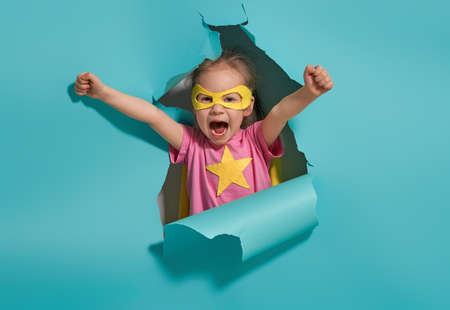 Little child playing superhero. Kid on the background of bright blue wall. Girl power concept. Yellow, pink and  turquoise colors. Imagens