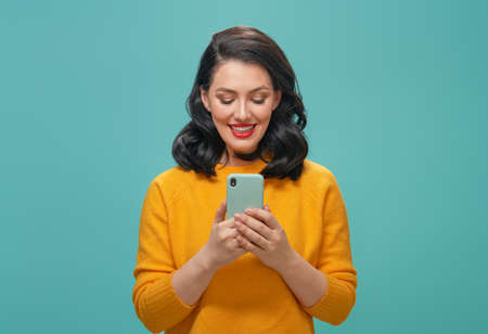 Smiling beautiful young woman in yellow sweater with mobile phone posing on turquoise background.