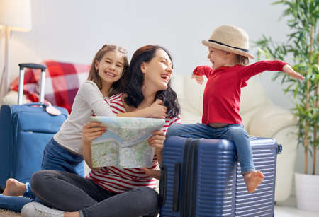 Go on an adventure! Happy family preparing for the journey. Mom and daughters are packing suitcases for the trip. Archivio Fotografico