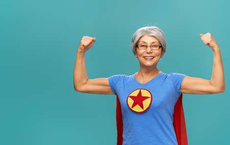 Joyful beautiful senior woman in superhero costume posing on turquoise background.