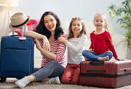 Go on an adventure! Happy family preparing for the journey. Mom and daughters are packing suitcases for the trip. 版權商用圖片