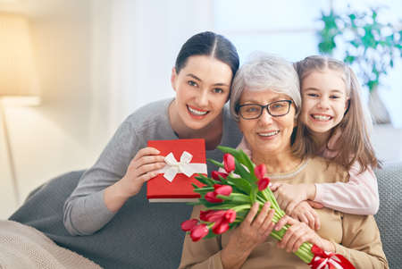 Happy women's day! Child daughter is congratulating mom and granny giving them flowers tulips. Grandma, mum and girl smiling and hugging. Family holiday and togetherness.