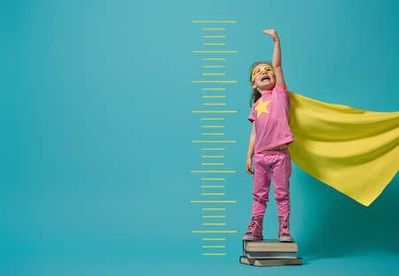 Kleines Kind, das Superhelden spielt. Kid misst das Wachstum auf dem Hintergrund der hellblauen Wand. Girl-Power-Konzept. Gelb, Rosa und Türkisfarben.