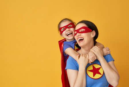 Moeder en haar kind spelen samen. Meisje en moeder in superheldenkostuums. Moeder en kind hebben plezier en glimlachen. Familie vakantie en samenzijn. Stockfoto