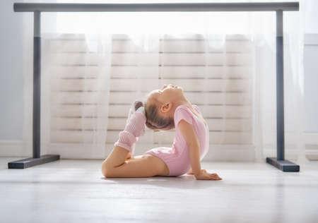 La bambina sveglia sogna di diventare una ballerina. Ragazza del bambino in un tutù rosa che balla in una stanza. La neonata sta studiando il balletto.