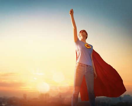 Gioiosa bella giovane donna in costume da supereroe in posa su sfondo tramonto.