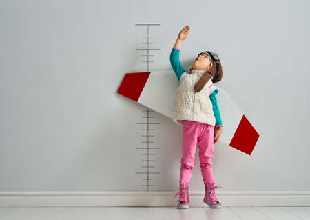 Little child is playing pilot. Kid is measuring the growth on the background of wall. Stockfoto - 117206425