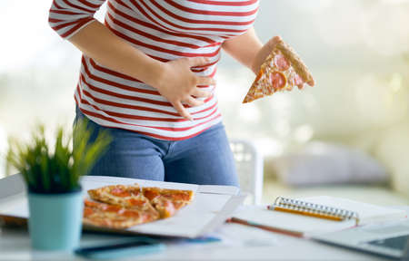 Woman eating pizza on the desk at work and having stomach problems.