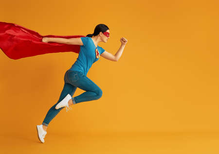 Joyful beautiful young woman in superhero costume posing on yellow background.